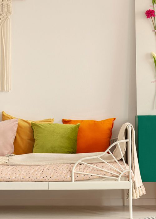 Handmade flower board on green wooden cabinet with leaf in glass vase next to comfortable bed with olive green, pastel pink, yellow and orange pillows; Shutterstock ID 1379171591; Purchase Order: -
