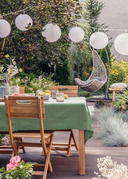 White paper lamps above garden table with chairs on stylish terrace with wooden floor and plants; Shutterstock ID 1410619058; Purchase Order: -