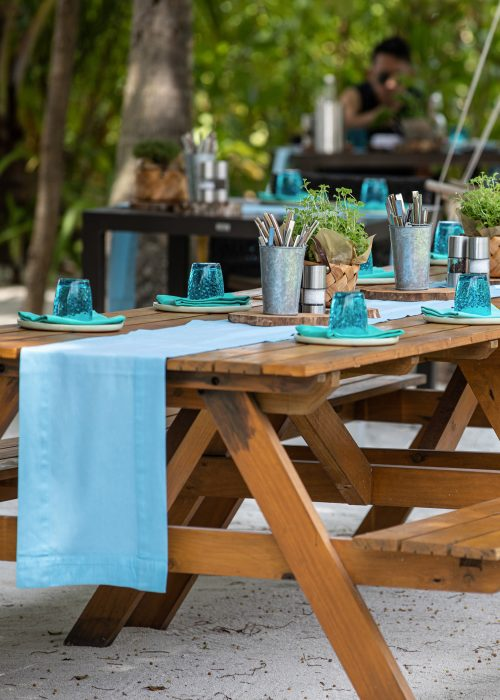 A beach blue outdoor terrace table setting for a bbq beachside dinner in the sand; Shutterstock ID 1665864484; Purchase Order: -